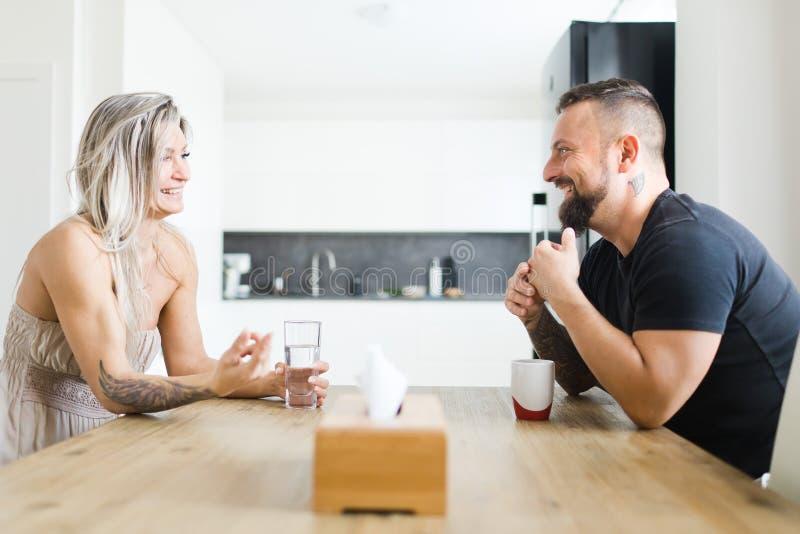 Hombre y mujer que se sientan por la tabla en lado opuesto y que discuten problemas de la familia imagen de archivo libre de regalías