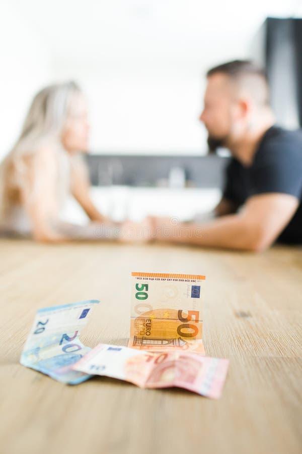 Hombre y mujer que se sientan por la tabla en lado opuesto y que discuten problemas financieros imagen de archivo