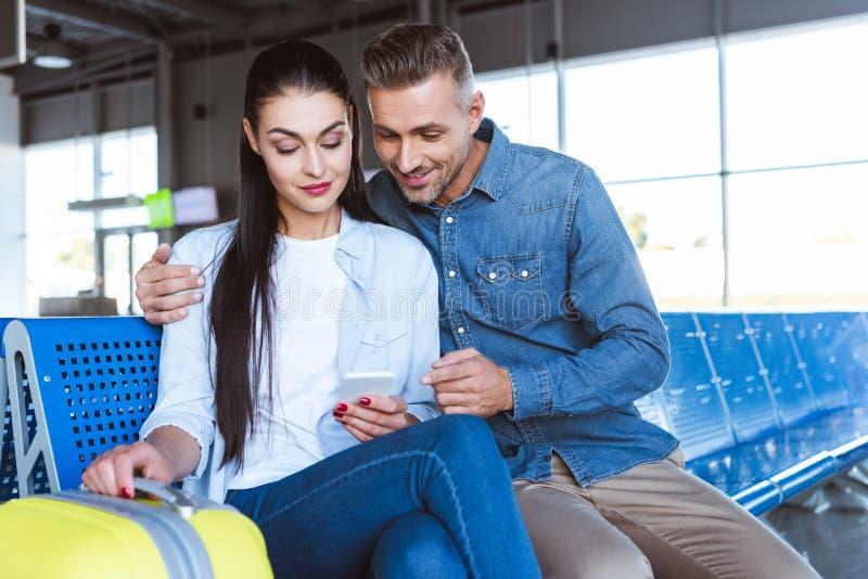 Hombre y mujer que sientan y que usan smartphone foto de archivo