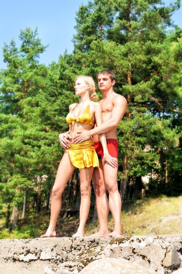 Hombre y mujer que sostienen encendido la playa. foto de archivo libre de regalías
