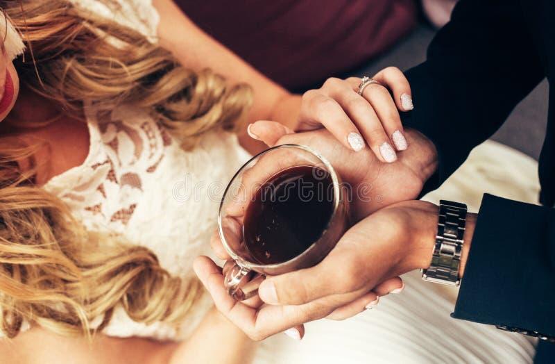 Hombre y mujer que sostienen la taza de café en las manos, opinión superior del primer fotos de archivo