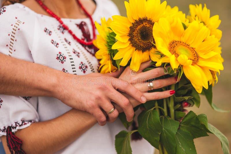 Hombre y mujer que sostienen un ramo de girasoles boda ucraniana imagen de archivo