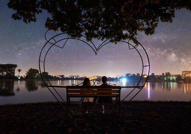 Hombre y mujer que tienen un resto en orilla debajo del cielo nocturno fotos de archivo libres de regalías