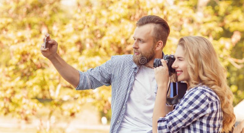 Hombre y mujer que toman las fotos con una cámara y un smartphone en parque del otoño fotos de archivo libres de regalías