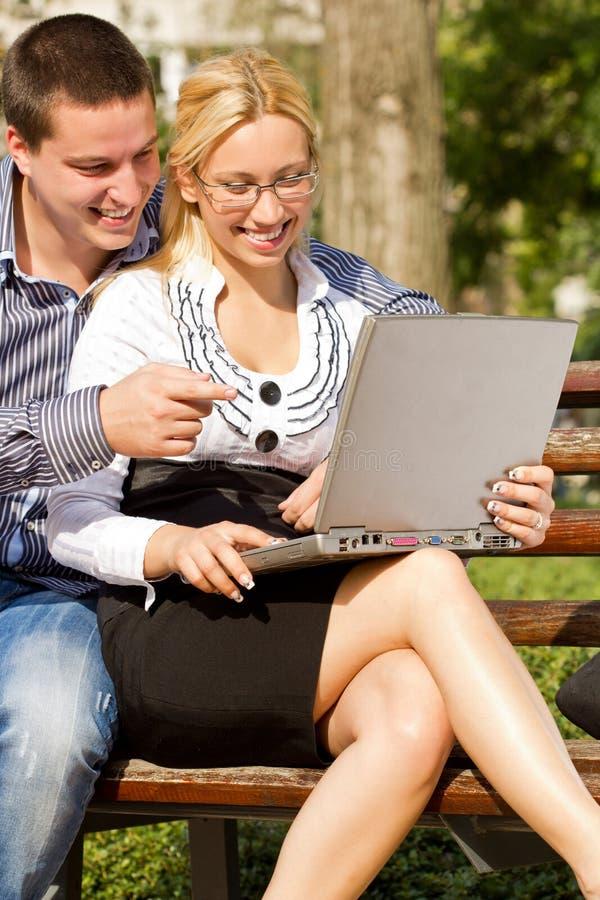 Hombre y mujer que trabajan en la computadora portátil en el parque fotografía de archivo libre de regalías