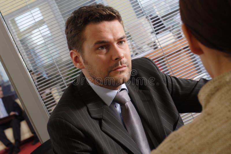 Hombre y mujer serios de negocios blanco que hablan en la oficina   foto de archivo libre de regalías