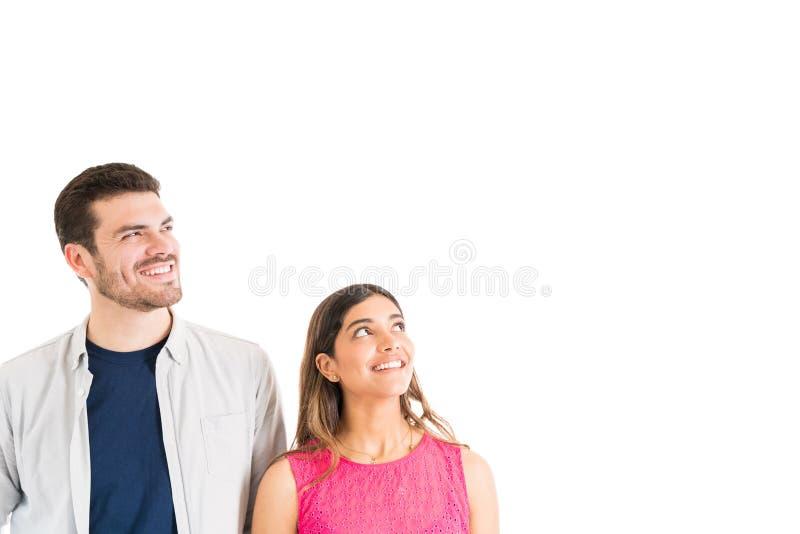 Hombre y mujer sonrientes que miran fijamente algo en estudio fotos de archivo libres de regalías