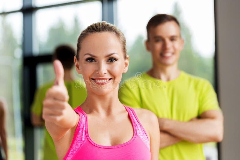 Hombre y mujer sonrientes que muestran los pulgares para arriba en gimnasio imagen de archivo libre de regalías