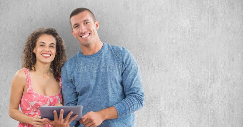 Hombre y mujer sonrientes que usa la tableta contra la pared imagen de archivo