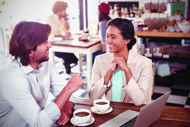 Hombre y mujer sonrientes que usa un ordenador portátil mientras que comiendo la taza de café fotos de archivo libres de regalías