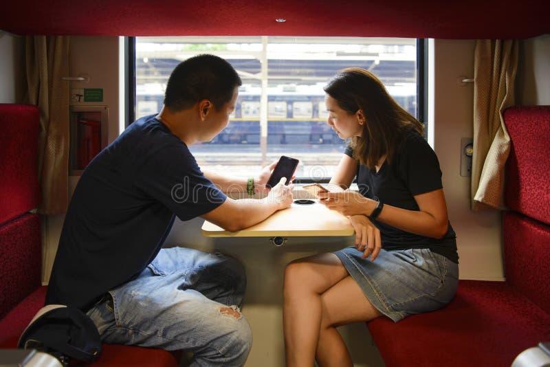 Hombre y mujer turísticos jovenes que usa en el teléfono en el tren mientras que viaje foto de archivo libre de regalías