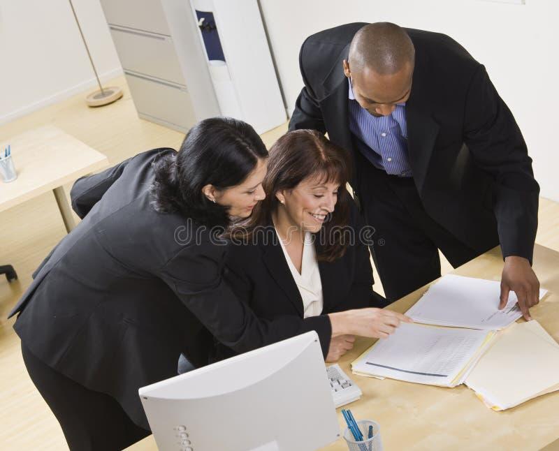 Hombre y mujeres que trabajan en oficina foto de archivo libre de regalías