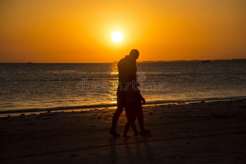 Hombre y niño de la silueta en la playa en la puesta del sol imagen de archivo libre de regalías