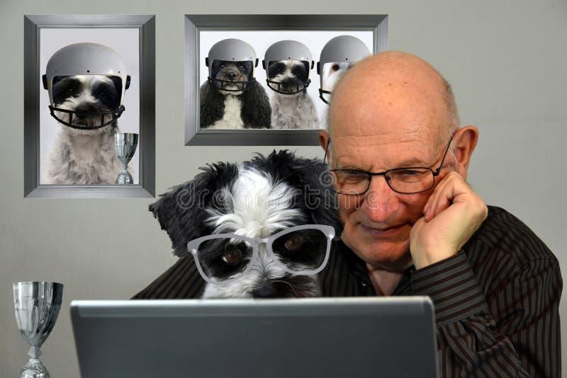Hombre y perro que miran resultados del fútbol en Internet fotografía de archivo libre de regalías