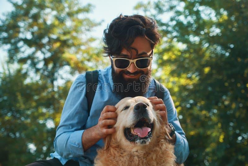 Hombre y perro que se divierten, el jugar, haciendo caras divertidas mientras que restin imagen de archivo