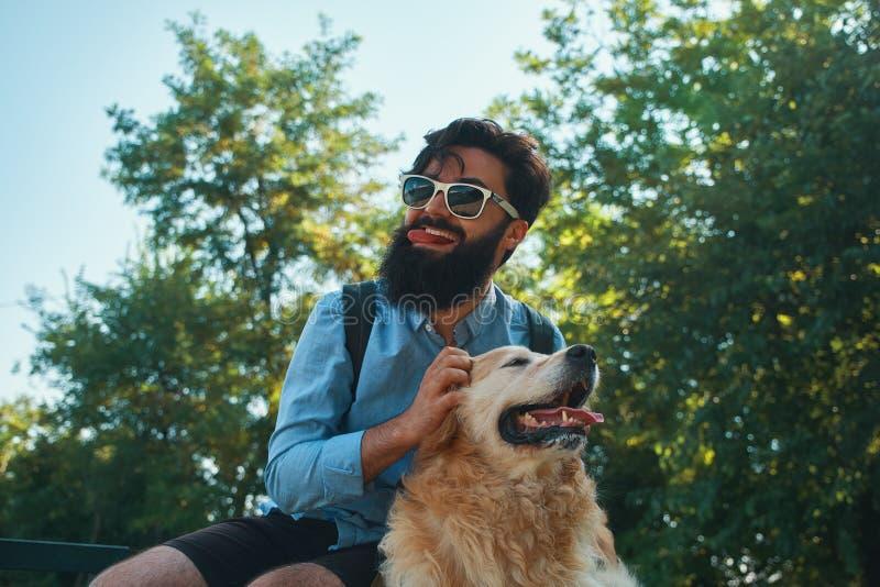 Hombre y perro que se divierten, el jugar, haciendo caras divertidas mientras que restin imágenes de archivo libres de regalías