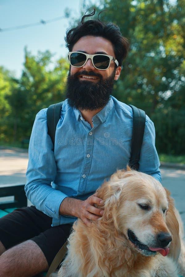 Hombre y perro que se divierten, el jugar, haciendo caras divertidas mientras que restin fotos de archivo