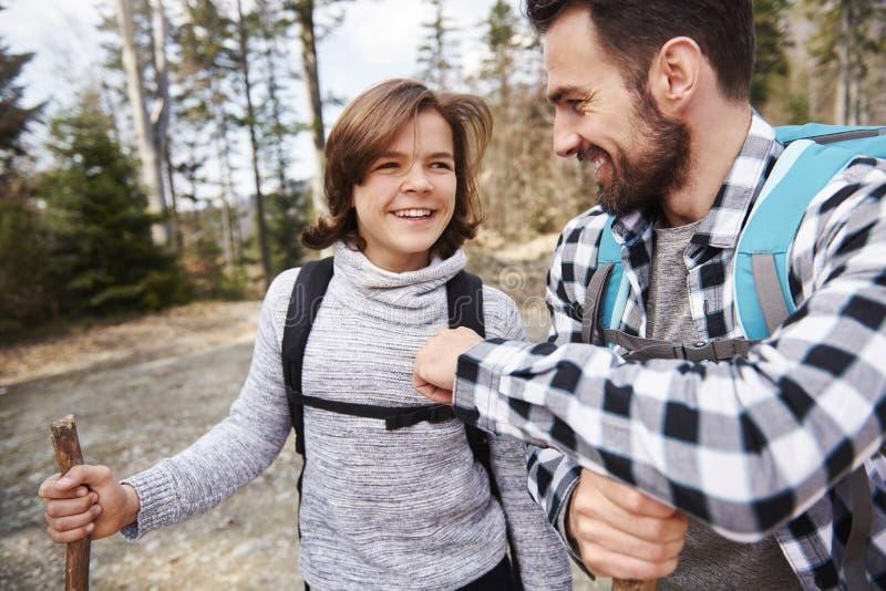 Hombre y su hijo adolescente que se divierten durante caminar viaje imagenes de archivo