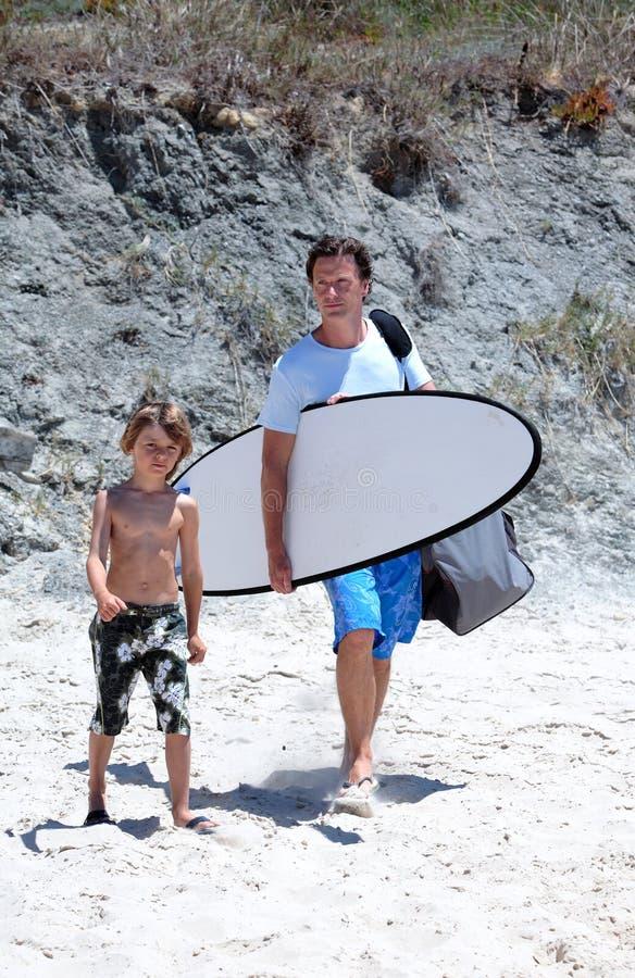 Hombre y su hijo que llegan la playa para practicar surf imágenes de archivo libres de regalías