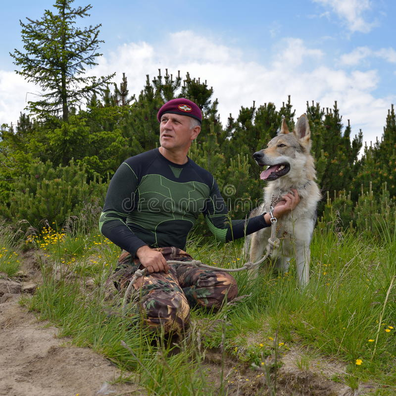 Hombre y su perro checoslovaco criado en línea pura del lobo fotos de archivo