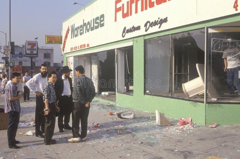 Hombres étnicos observando la tienda de muebles saqueada durante 1992 alborotos, Los Ángeles central del sur, California foto de archivo libre de regalías
