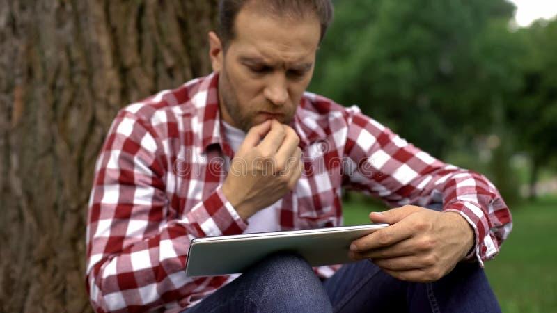 Hombres adultos concentrados que usan la tableta en el parque, artículo de la lectura acerca de la salud para hombre imagenes de archivo