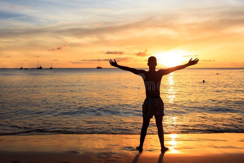 Hombres africanos que aumentan los brazos para arriba en la puesta del sol en la playa de Tarrafal en San imagen de archivo