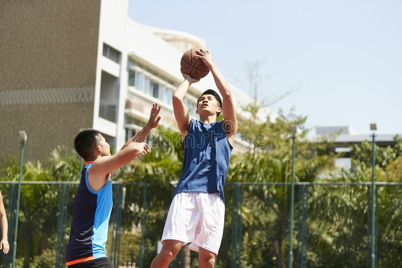 Hombres asiáticos jovenes que juegan a baloncesto foto de archivo