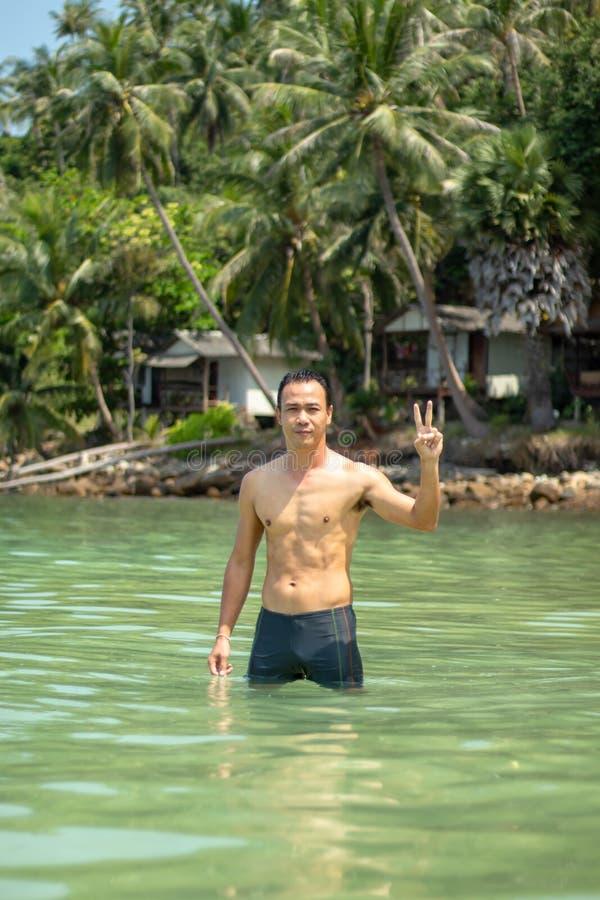 Hombres asiáticos que nadan en las rocas y los árboles del fondo del mar imagenes de archivo