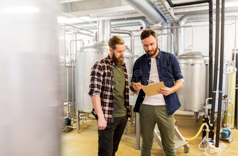 Hombres con el tablero en la cervecería del arte o la planta de la cerveza fotos de archivo