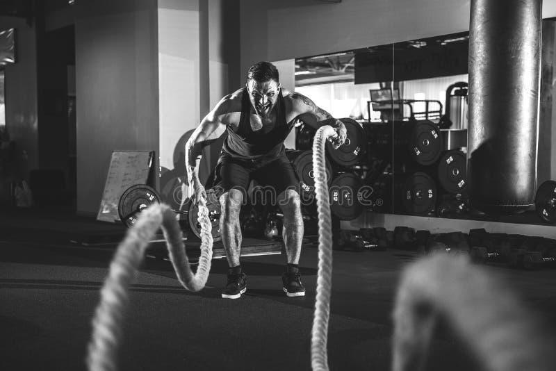 Hombres con la cuerda en gimnasio funcional del entrenamiento foto de archivo libre de regalías