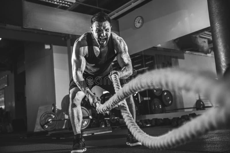 Hombres con la cuerda en gimnasio funcional del entrenamiento fotografía de archivo