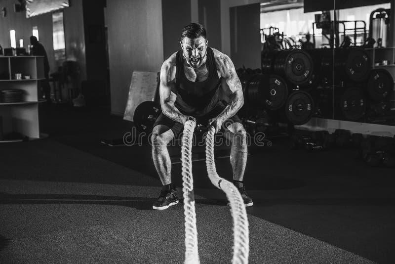 Hombres con la cuerda en gimnasio funcional del entrenamiento imagenes de archivo