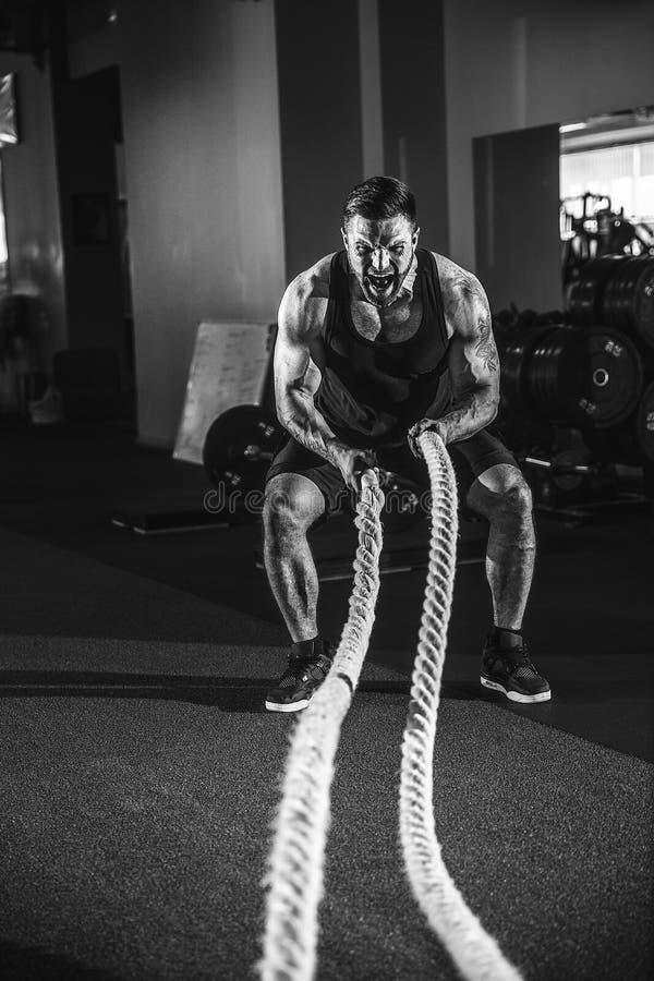 Hombres con la cuerda en gimnasio funcional del entrenamiento imagen de archivo libre de regalías