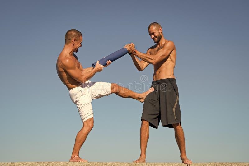 Hombres con la estera de la yoga capturada en fondo del cielo azul del movimiento El luchar del deportista Habilidades que luchan fotografía de archivo libre de regalías