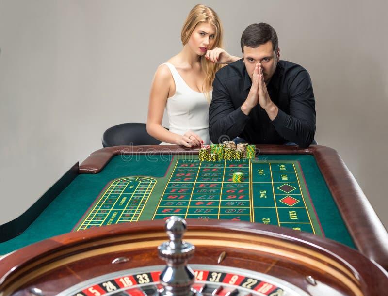 Hombres con las mujeres que juegan la ruleta en el casino imagen de archivo