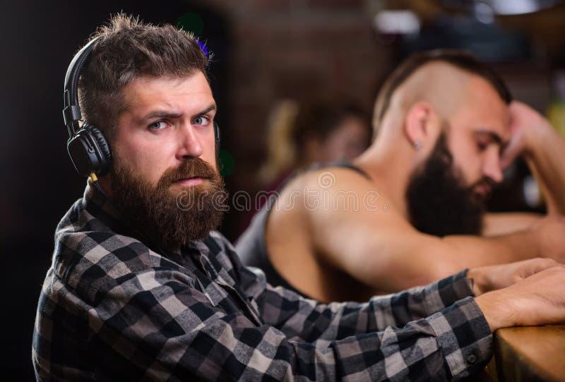 Hombres con los auriculares y smartphone que se relaja en la barra Evite la comunicación Realidad del escape Relajación de vierne fotos de archivo libres de regalías