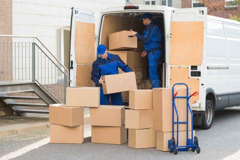 Hombres de entrega que descargan las cajas en la calle imagenes de archivo
