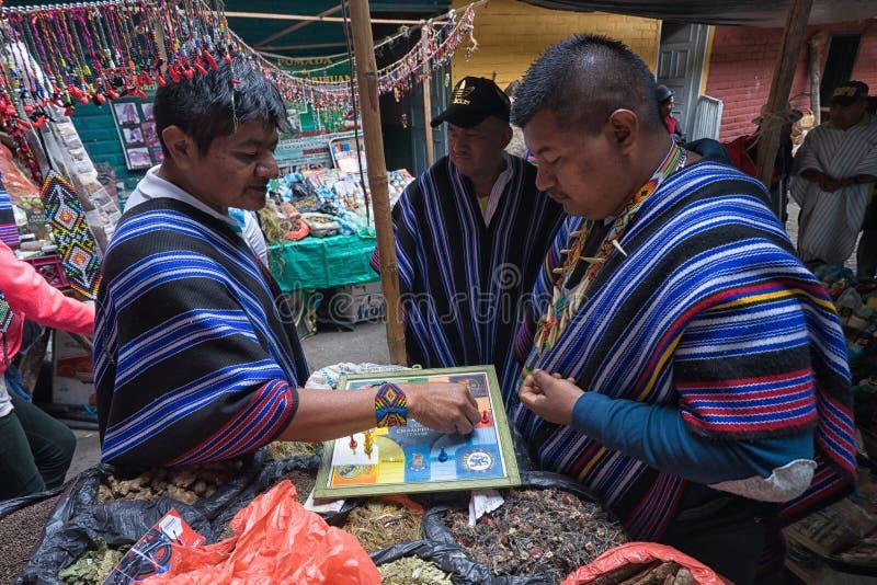 Hombres de Guambiano que juegan al juego de mesa en Silvia, Colombia fotos de archivo