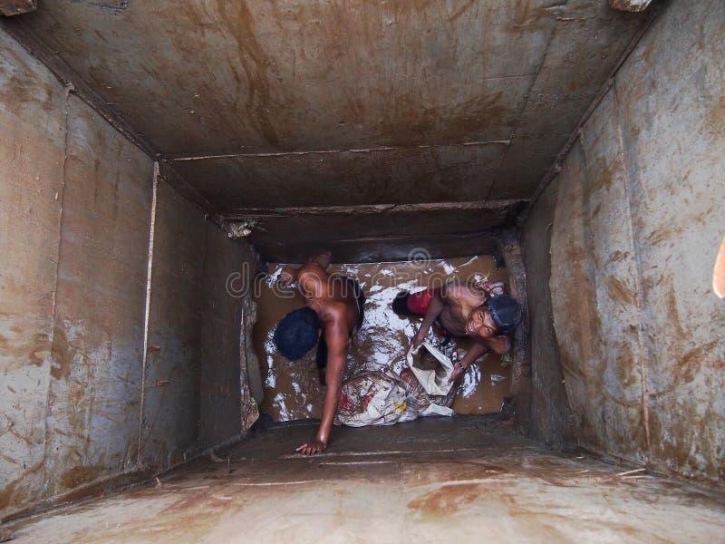 Hombres de la construcción que trabajan dentro de un alcantarillado del camino fotos de archivo