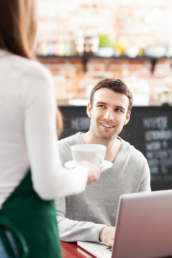 Hombre joven que es servido en el café fotos de archivo libres de regalías