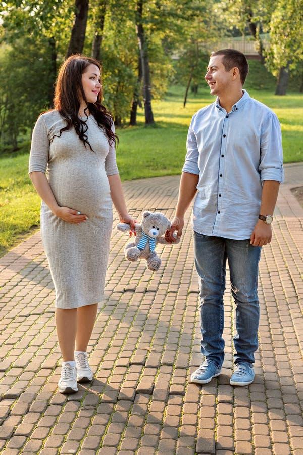 Hombres de los pares de la familia y una mujer embarazada joven que camina sosteniendo el juguete del oso de peluche en el parque imagenes de archivo