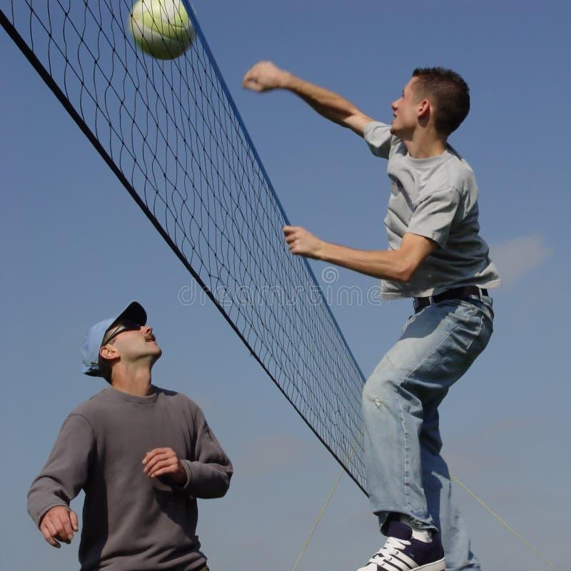 Hombres de los pares que juegan a voleibol fotografía de archivo
