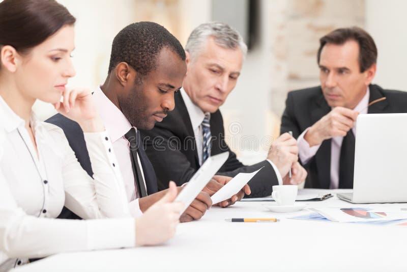 Hombres de negocios étnicos multi que discuten el trabajo foto de archivo