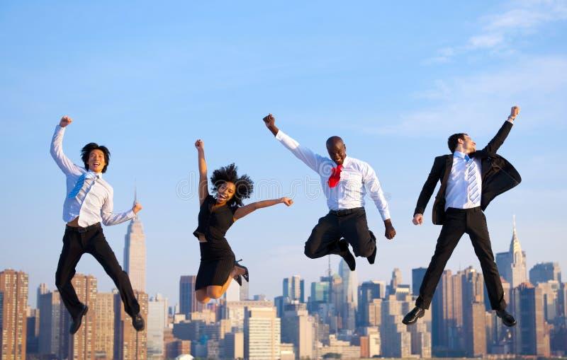 Hombres de negocios acertados felices que celebran saltando en nueva Y fotografía de archivo libre de regalías