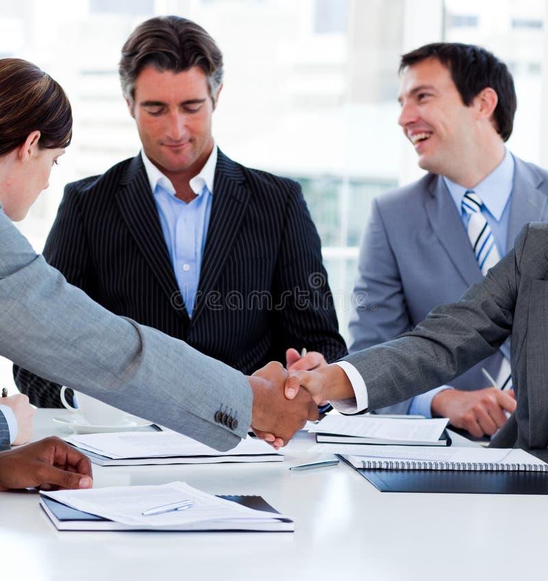 Hombres de negocios acertados que cierran un reparto imagen de archivo