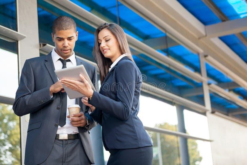 Hombres de negocios acertados serios jovenes con el talkin de la tableta foto de archivo libre de regalías