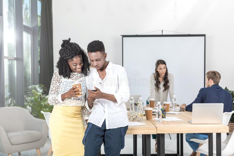 hombres de negocios afroamericanos sonrientes que usan smartphone junto imágenes de archivo libres de regalías