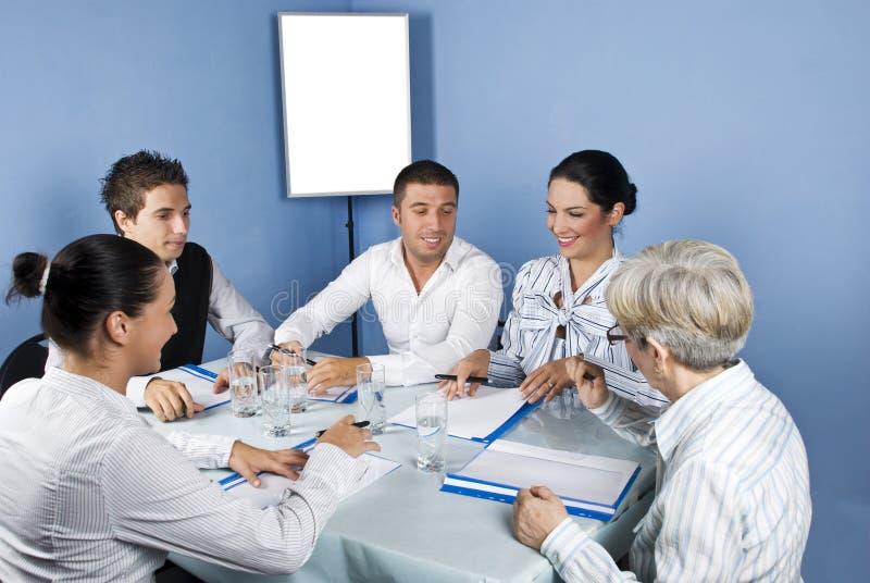 Hombres de negocios alrededor de un vector en la reunión imágenes de archivo libres de regalías