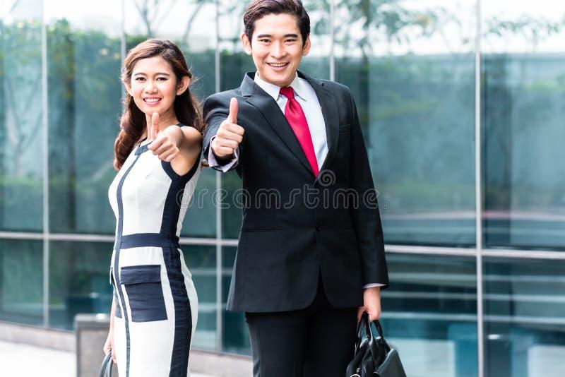 Hombres de negocios asiáticos afuera delante del edificio imagenes de archivo